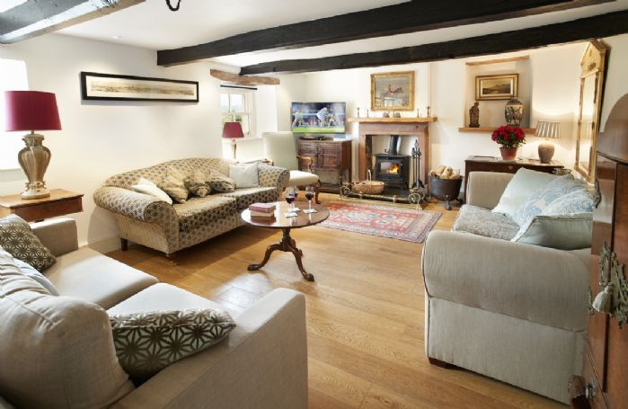 Ground floor: Sitting Room with exposed beams and wood burning stove