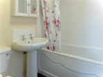 The bathroom with a bath and overhead shower, WC and hand basin.