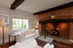 Ground floor: Sitting area with open fireplace and contemporary, realistic electric log fire