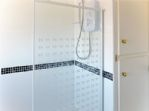 The clean and modern over-bath shower and useful airing cupboard.
