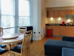 The dining area with the open plan kitchen in view.
