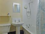 Smart white bathroom suiute with bath and overhead shower.