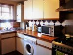The kitchen has an oven, hob, microwave, fridge/freezer and washer.