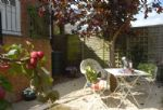 Outside: A small private patio/garden area provides seating to enjoy alfresco dining