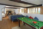 A view of the pool table looking towards the fireplace