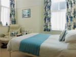 The double bed and easy chair in this large, sunny room.