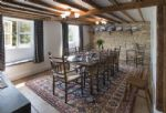 Ground floor:  Dining room overlooking the garden with exposed Cotswold stone wall, beams and old wooden floor