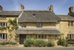 Inglenook Cottage, a pretty, thatched, terraced 300 year old Grade II Listed Cotswold stone former smithy