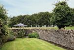 A path from the back door leads to the walled garden, with patio and pleasant views over the fields