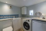 Utility room features a washing machine and WC