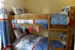 A pretty bunk room is the first of two bedrooms on the first floor.