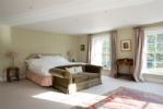 The sizable master bedroom with views across the gardens