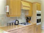 A large fully-equipped kitchen with gas hob and fridge with separate upright freezer.