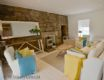 Mangle Cottage has a spacious and comfortable living area with feature stone wall