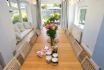 Sun room has a long wooden dining table, seating 10