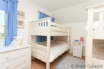 White painted bunk beds aimed at providing accommodation for four children (but are adult-sized)