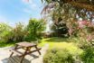 Spacious garden with outdoor table and benches ideal for eating outdoors
